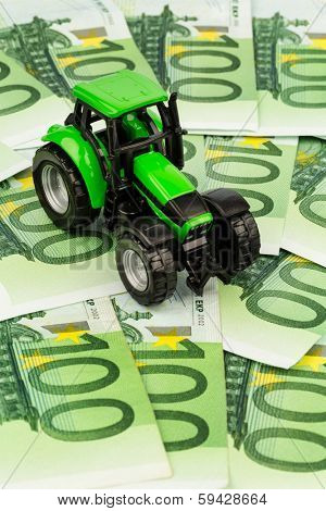 a tractor standing on euro banknotes. symbolic photo for costs, revenues and subsidies a farmer in agriculture