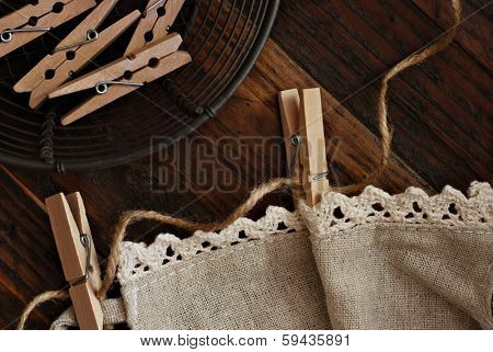'Laundry day' still life includes wooden clothespins with twine, homespun fabric with crochet edging, and vintage basket on rustic, dark wood background.  Low key natural lighting for effect.