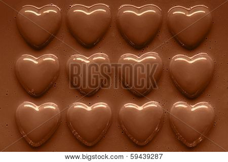 Photo of chocolate hearts in a row smothered in smooth melted milk chocolate