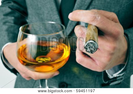 a man wearing a suit with a cigar and a glass with brandy