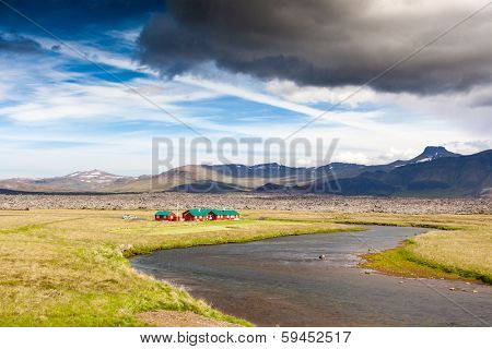 Red houses next a river in icelandic countryside. Summer season, Iceland