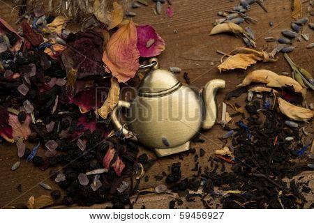 Teapot trinket among flower tea petals on wooden table background