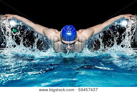 Muscular young man in blue cap in swimming pool