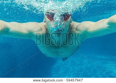 Man in swim cap and googles under water in swimming pool