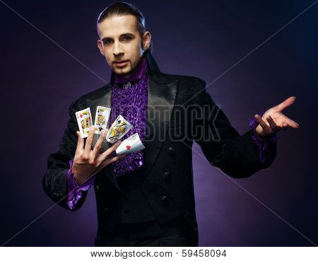 Young brunette magician in stage costume showing card tricks