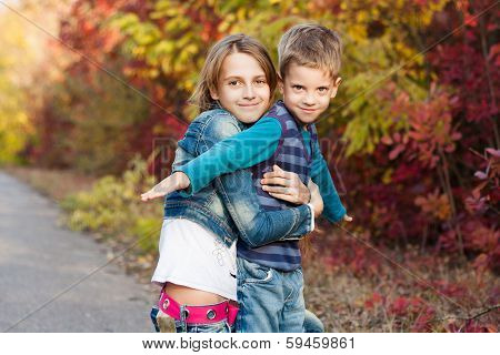 Young sister with little brother in the autumn park.