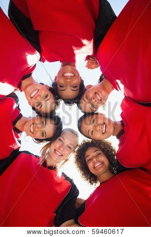Directly below shot of happy female soccer team forming huddle against clear sky
