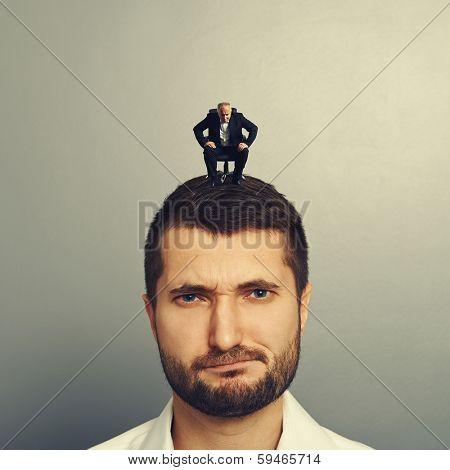 small senior businessman looking at big displeased man