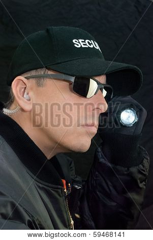 Security Guard Searches With Flashlight
