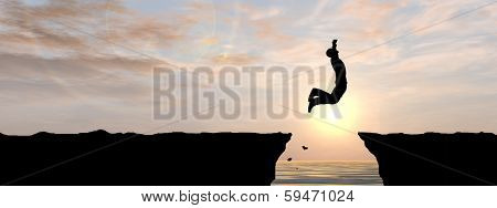 Concept or conceptual young man, businessman silhouette jump happy from cliff over water gap sunset or sunrise sky background, metaphor to freedom, nature, mountain, success, free, joy, health or risk