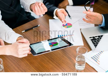 Business - banker, Manager or expert in meeting evaluates the figures on tablet computer and compares the development of the business to advise and act as consultant