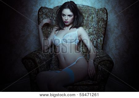 Beautiful provocative woman in lingerie sitting in an antique armchair with a highlight to her upper body