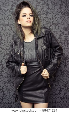 Sexy trendy young brunette woman in a leather jacket and miniskirt posing provocatively for the camera on a dark background