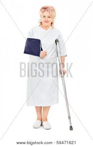 Full length portrait of female patient with broken arm standing with a crutch isolated on white background