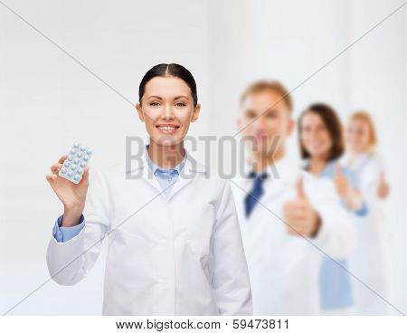 healthcare, medicine and pharmacy concept - smiling female doctor and with pills