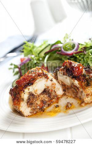 Stuffed chicken breast with salad.  Sundried tomato and mozzarella filling.