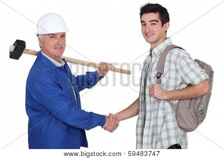 senior craftsman and apprentice shaking hands