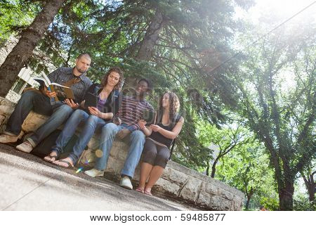 Full length of multiethnic students studying on parapet at university campus