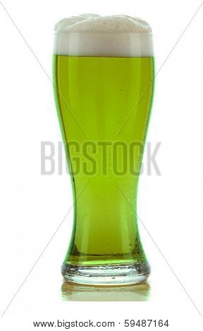 A cold frothy glass of green beer for St. Patricks Day isolated on white with a slight reflection.