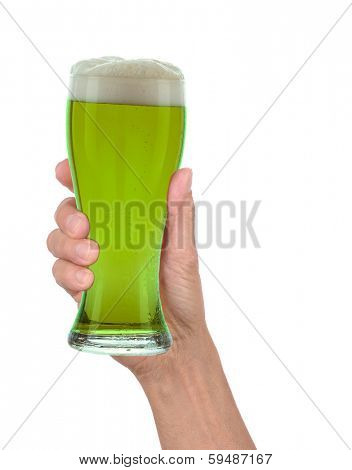 Man's hand holding up a glass of foamy green beer to celebrate St. Patrick's Day. Vertical format over a white background