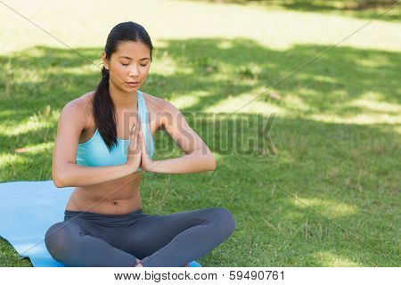 View of a sporty young woman in Namaste position with eyes closed at the park