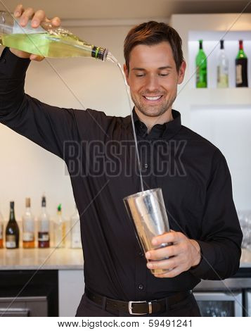 Happy bartender preparing a cocktail at the bar