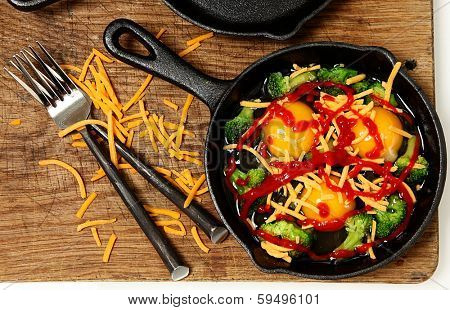 Uncooked Raw Eggs in Skillet with Brocolli, Cheese and Sriracha Sauce ready to put in oven.