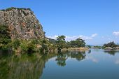 stock photo of dalyan  - The rock blue sky and green trees glassed in the water of Dalyan river  - JPG