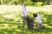 stock photo of pick up  - Two young volunteers picking up litter in the park - JPG