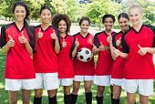 stock photo of united we stand  - Portrait of successful female soccer team gesturing thumbs up at park - JPG