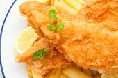 stock photo of hake  - Two pieces of freshly fried fish with chips and a slice of lemon - JPG