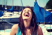 stock photo of laugh out loud  - Happy girl in front of yacht boat is laughing with closed eyes - JPG