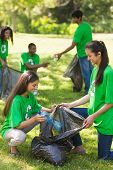 stock photo of kneeling  - Team of young volunteers picking up litter in the park - JPG