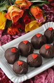 foto of red velvet cake  - Red Velvet Cake Pops with roses in the background - JPG