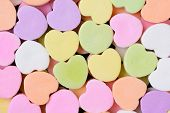 Macro shot of pastel candy hearts for Valentine's Day. The hearts are all bland and ready for your m