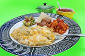 pic of enchiladas  - Fork with bite of Chicken enchiladas in green sauce with beans; rice; and guacomole on black and white plate in geometric design -- probably Aztec. Enchiladas Verde.
