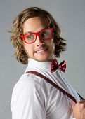 stock photo of bow tie hair  - Portrait of a handsome caucasian man wearing a white buttoned shirt red checkered bow tie suspenders and funky glasses - JPG