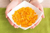 Woman's hands holding bowl of cornflakes