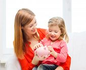 family, children, money, investmen and happy people concept - happy mother and daughter with small p