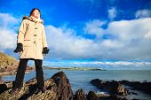 stock photo of ireland  - Woman tourist standing on rock cliff watching the ocean looking to sun enjoying sunny day peaceful relaxing. Church Bay Co. Cork Ireland Europe