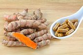 picture of rhizomes  - Fresh Turmeric rhizomes next to a spoon of Turmeric Capsules - JPG