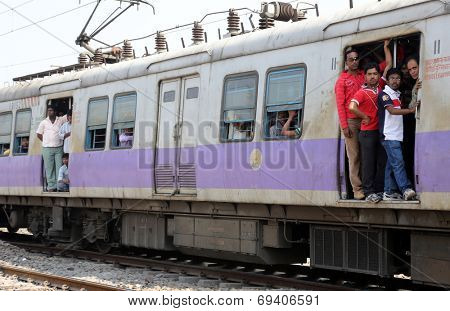 KOLKATA, INDIA - FEBRUARY 09: Unidentified locals and tourists commute by train on February 15, 2014 in Kolkata, India. Commuters on a busy train seek the breeze by an open doorway.