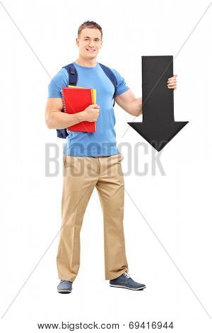 Full length portrait of a male student holding a big black arrow pointing down isolated on white background