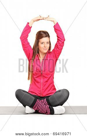 Young woman exercising yoga seated on a mat isolated on white background