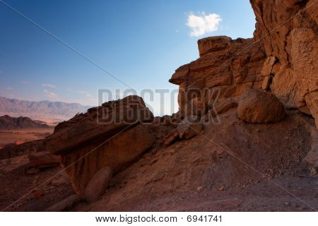 Scenic weathered orange rock in stone desert on sunset