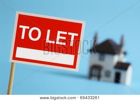 Real estate agent to let sign with house in background