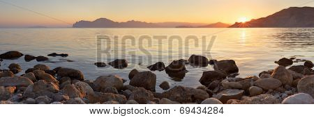 Landscape panorama at sunset. Sea shore with stones. A warm summer evening
