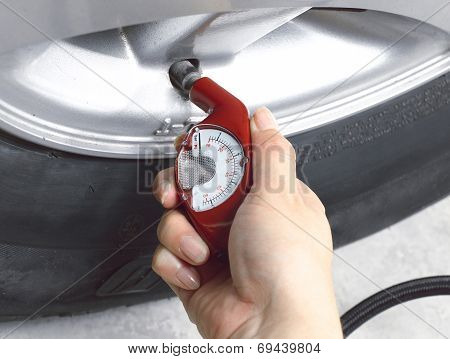 woman checking her air tire pressure