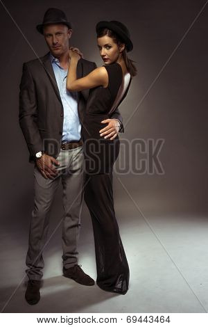 Attractive sexy couple in trendy evening wear on a romantic night out standing in an intimate embrace with the suave young man looking down at the floor as the woman turns to look over her shoulder