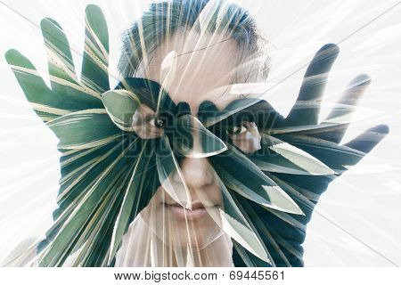 Double exposure portrait of attractive woman in black gloves forming glasses combined with photograph of cactus